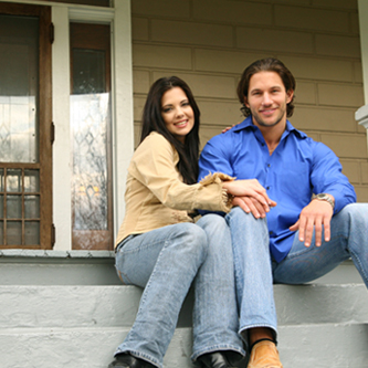 Young couple sitting on the stairs outside of their home.