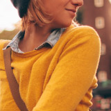Close up of a woman in a yellow sweater.