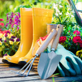 Close up of garden boots and tools outside.