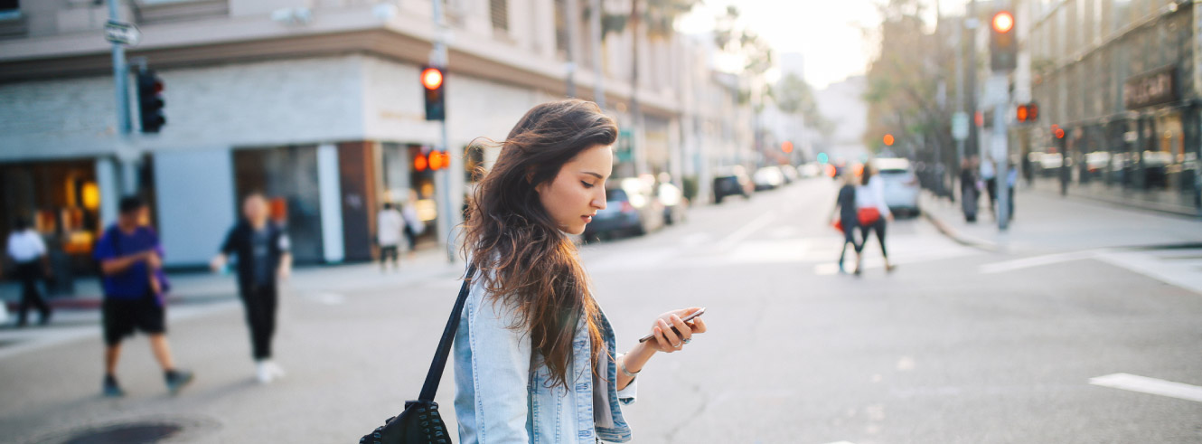 Young woman crossing an intersection. She is looking down at her phone.