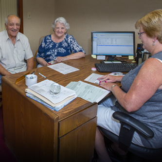 Senior couple sitting at the desk of a team member from Cayuga Lake National Bank.