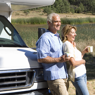 An older couple standing outside with coffee mug leaning against an RV.