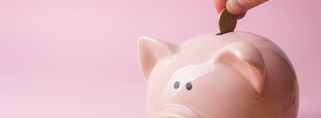 Hand placing a coin in a pink piggy bank.