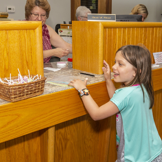 Young girl standing at a bank teller window with her eyes on a basket of candy.