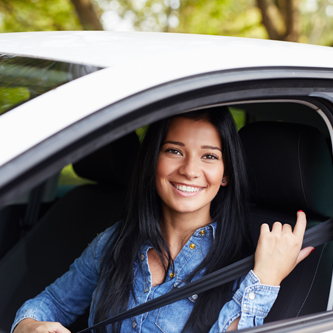 Young woman pulling her seatbelt on inside of a car, she is smiling at the camera.