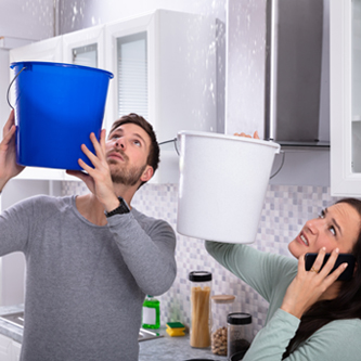 Couple holding buckets to catch water falling from the ceiling.
